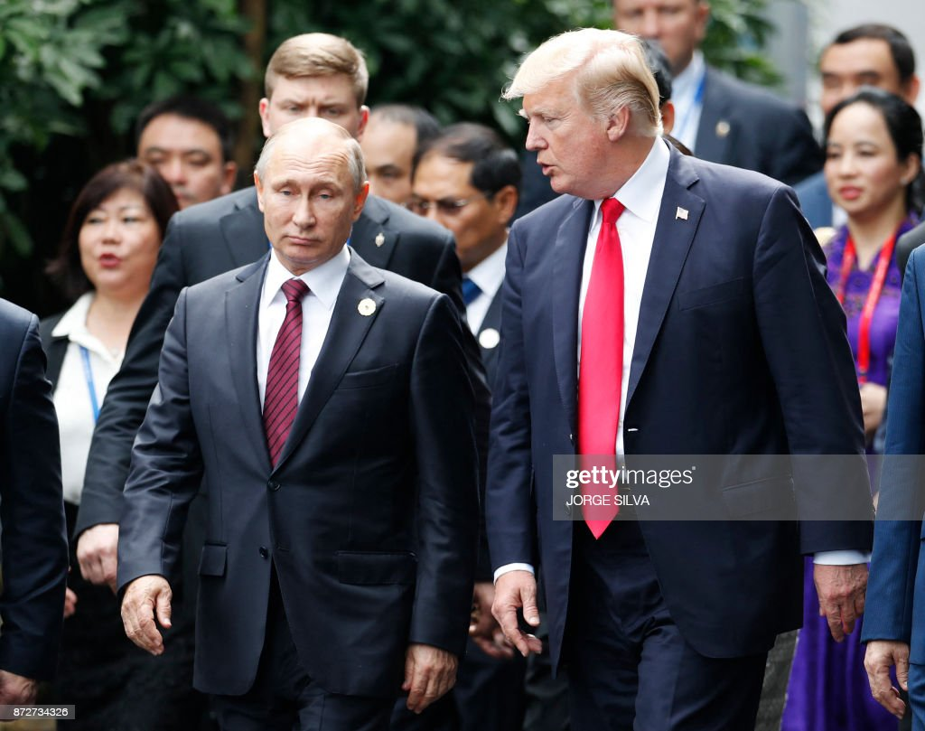 US President Donald Trump (R) and Russia's President Vladimir Putin talk as the make their way to take the 'family photo' during the Asia-Pacific Economic Cooperation (APEC) leaders' summit in the central Vietnamese city of Danang on November 11, 2017. World leaders and senior business figures are gathering in the Vietnamese city of Danang this week for the annual 21-member APEC summit. /