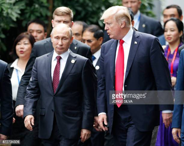 US President Donald Trump and Russia's President Vladimir Putin talk as the make their way to take the 'family photo' during the AsiaPacific Economic...