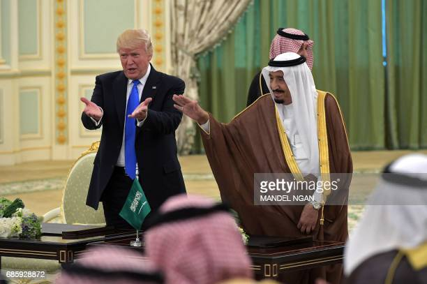 US President Donald Trump and Saudi Arabia's King Salman bin Abdulaziz alSaud gesture during a signing ceremony at the Saudi Royal Court in Riyadh on...