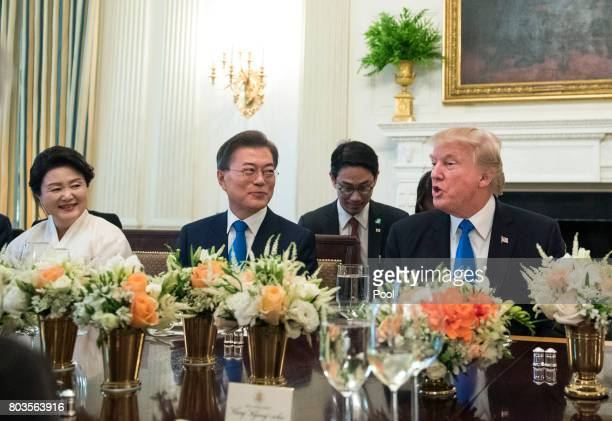 US President Donald Trump and South Korean President Moon Jaein address the media prior to dinner as Moon's wife Kim Jeongsuk watches in the State...