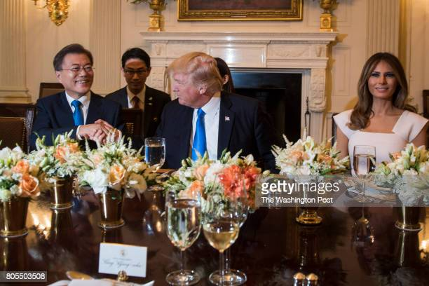 President Donald Trump and South Korean President Moon Jaein shakes hands as First Lady Melania Trump and President Moon's wife Kim Jeongsuk watch...