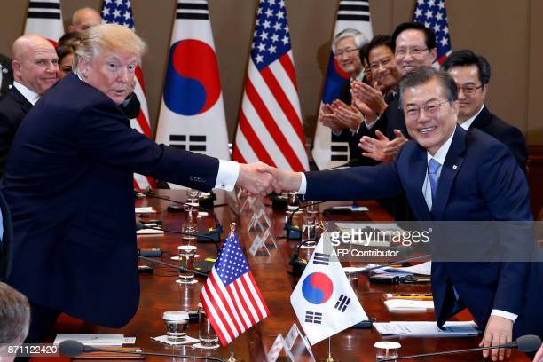 US President Donald Trump and South Korea's President Moon JaeIn shake hands before their summit meeting at the presidential Blue House in Seoul on...