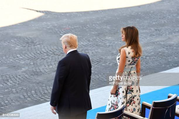 US President Donald Trump and US First Lady Melania Trump stand ahead of the start of the annual Bastille Day military parade on the ChampsElysees...