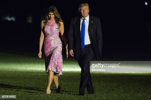 US President Donald Trump and US First Lady Melania Trump walk across the South Lawn of the White House in Washington DC US on Tuesday July 25 2017...