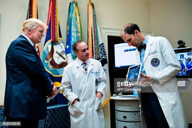 US President Donald Trump and US Secretary of Veterans Affairs David J Shulkin watch a video conference with a patient after speaking about new...