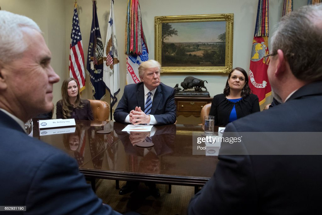 President Donald Trump and Vice President Mike Pence (front-L) attend a meeting on healthcare with Brittany Ivey (back-L) of Georgia, Carrie Couey (back-R) of Colorado and Greg Knox (front-R) of Ohio in the Roosevelt Room of the White House on March 13, 2017 in Washington, DC. The House Republicans' bill known as the 'American Health Care Act', which is intended to replace the Affordable Care Act and is endorsed by President Trump, has faced criticism from both Republicans and Democrats.