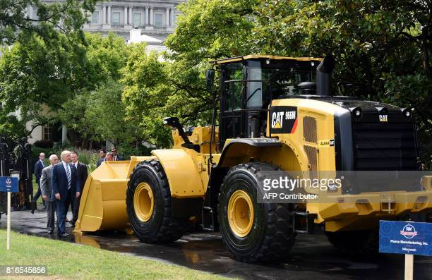 President Donald Trump and Vice President Mike Pence examine an iconic Yellow Iron from Caterpillar Inc during a 'Made in America' product showcase...