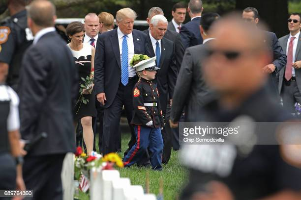 S President Donald Trump and Vice President Mike Pence follow 6yearold Christian Jacobs through Section 60 of Arlington National Cemetery on Memorial...