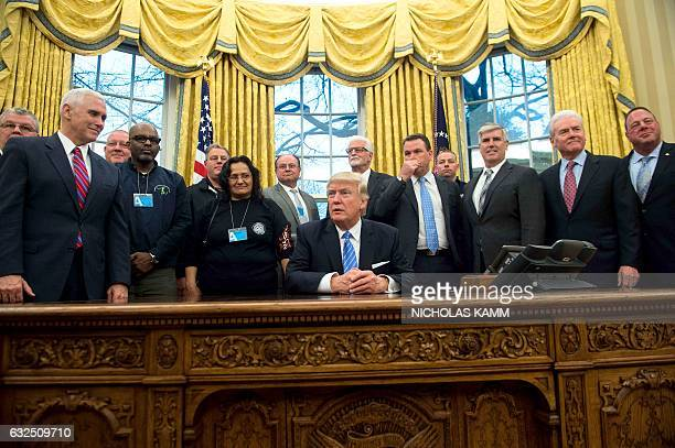 US President Donald Trump and Vice President Mike Pence pose with labor leaders on January 23 2017 in the Oval Office at the White House in...
