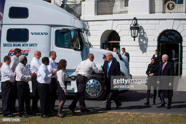 US President Donald Trump and Vice President Mike Pence walk out to welcome truckers and CEOs to the White House in Washington DC March 23 to discuss...