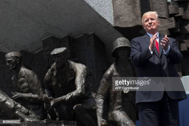 US President Donald Trump applauds as he stands in front of the Warsaw Uprising Monument on Krasinski Square during the Three Seas Initiative Summit...