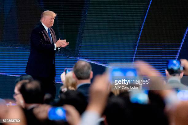 US President Donald Trump applauds during speech on the final day of the APEC CEO Summit part of the broader AsiaPacific Economic Cooperation...