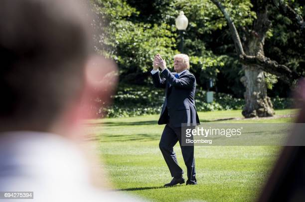 US President Donald Trump applauds while walking to Marine One on the South Lawn of the White House in Washington DC US on Friday June 9 2017...