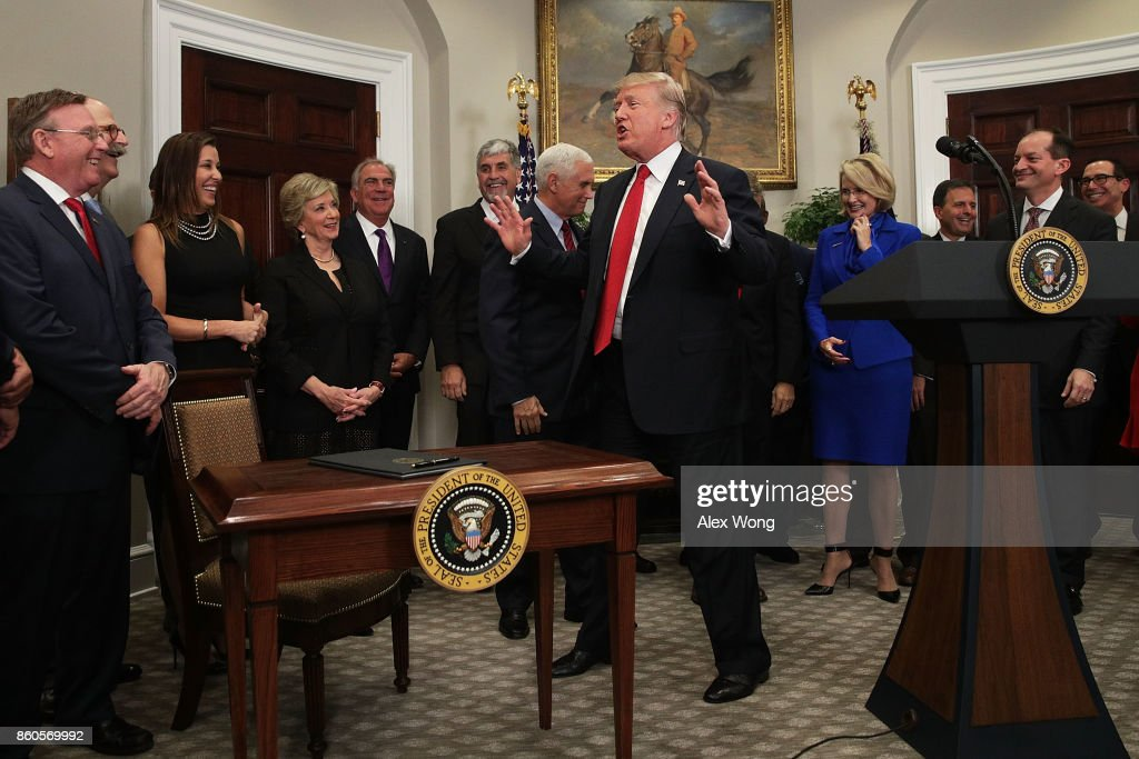 U.S. President Donald Trump approaches the signing table as he reacts after he forgot and was reminded to sign an executive order during an event in the Roosevelt Room of the White House October 12, 2017 in Washington, DC. President Trump signed the executive order to loosen restrictions on Affordable Care Act 'to promote healthcare choice and competition.'