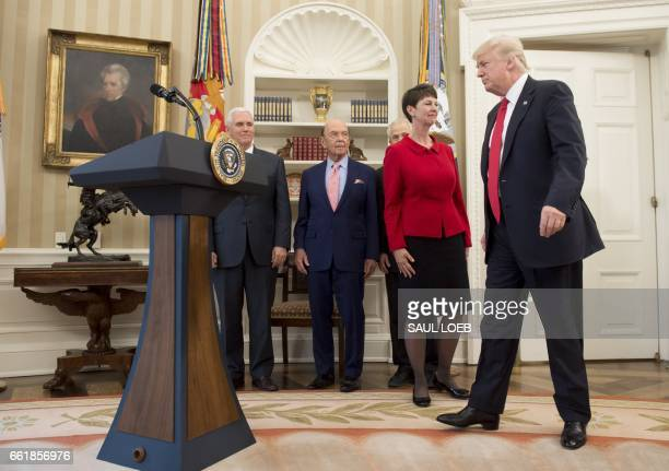 US President Donald Trump arrives alongside US Vice President Mike Pence Commerce Secretary Wilbur Ross and Peter Navarro director of the National...