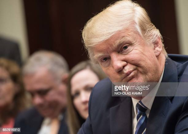 President Donald Trump attends a meeting about healthcare in the Roosevelt Room at the White House in Washington DC on March 13 2017 / AFP PHOTO /...