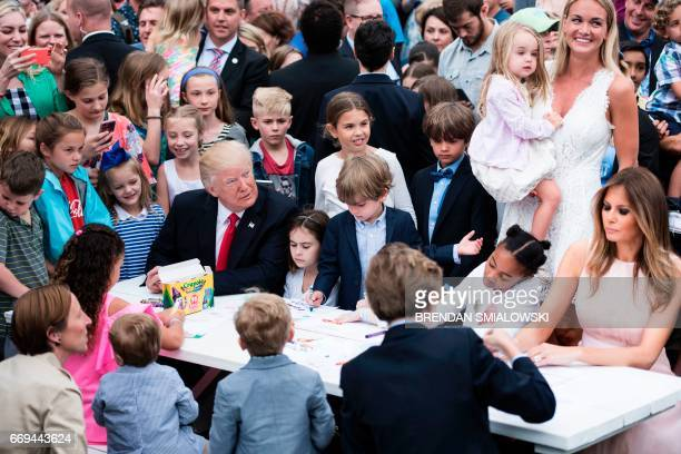 US President Donald Trump Barron Trump and US First Lady Melania Trump join others to write notes to service members during the Easter Egg Roll on...