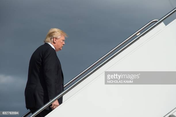 President Donald Trump boards Air Force One at Andrews Air Force Base in Maryland on January 26 2017 as he departs to attend a Republican retreat in...