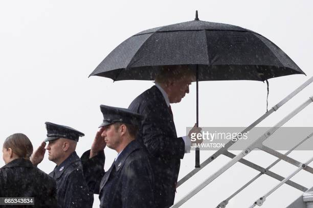 President Donald Trump boards Air Force One under heavy rain at Andrews Air Force Base Maryland April 6 2017 Donald Trump will host Chinese President...