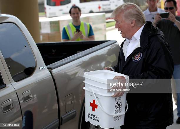 S President Donald Trump carries emergency supplies to a waiting pickip truck for residents impacted by Hurricane Harvey while visiting the First...
