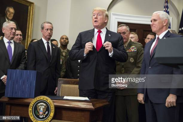US President Donald Trump center adjusts his jacket next to US Vice President Mike Pence right after signing the National Defense Authorization Act...