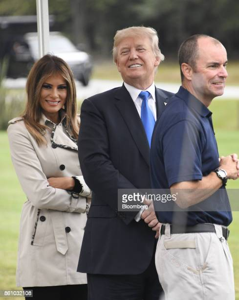 US President Donald Trump center and US First Lady Melania Trump smile while talking with an employee at a tour of the US Secret Service James J...