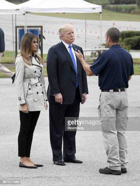 US President Donald Trump center and US First Lady Melania Trump speak with an employee while touring the US Secret Service James J Rowley Training...