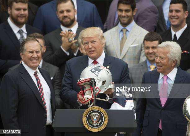 US President Donald Trump center displays a football helmet while speaking as Bill Belichick coach of the New England Patriots football team left and...