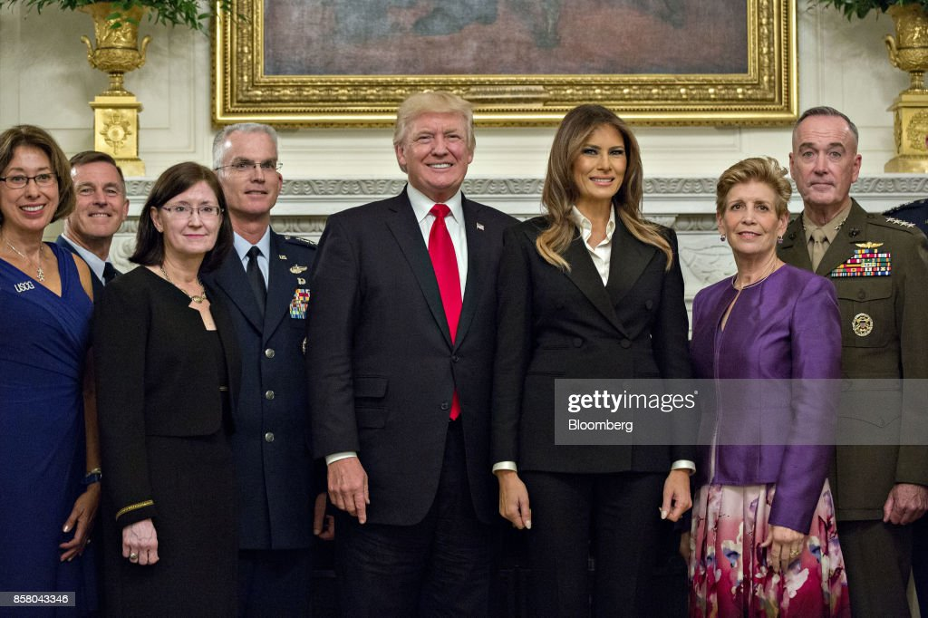 U.S. President Donald Trump, center left, and U.S. First Lady Melania Trump, center right, stand for an official photograph with senior military leaders and spouses including General Joseph Dunford, chairman of the Joint Chiefs of Staff, right, and General Paul Selva, vice chairman of the Joint Chiefs of Staff, fourth left, in the State Dining room of the White House in Washington, D.C., U.S., on Thursday, Oct. 5, 2017. President Trump and the First Lady are hosting the group for dinner in the Blue Room of the White House. Photographer: Andrew Harrer/Bloomberg via Getty Images