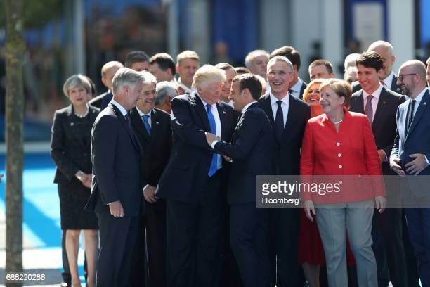US President Donald Trump center left shakes hands with Emmanuel Macron France's president as other world leaders look on at the North Atlantic...