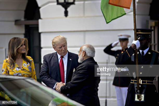US President Donald Trump center shakes hands Narendra Modi India's prime minister right with US First Lady Melania Trump at the South Portico of the...