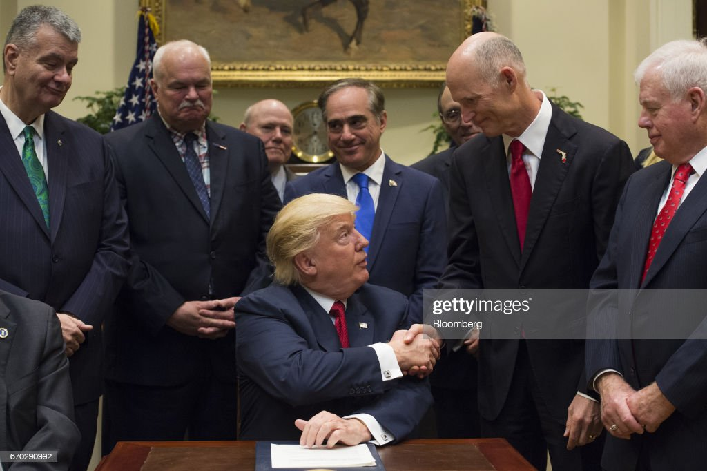 U.S. President Donald Trump, center, shakes hands with Rick Scott, governor of Florida, after signing bill S. 544, the Veterans Choice Program Extension and Improvement Act, in the Roosevelt Room of the White House in Washington, D.C., U.S., on Wednesday, April 19, 2017 The bill extends a program allowing eligible veterans to seek medical care from private health-care providers. Photographer: Molly Riley/Pool via Bloomberg