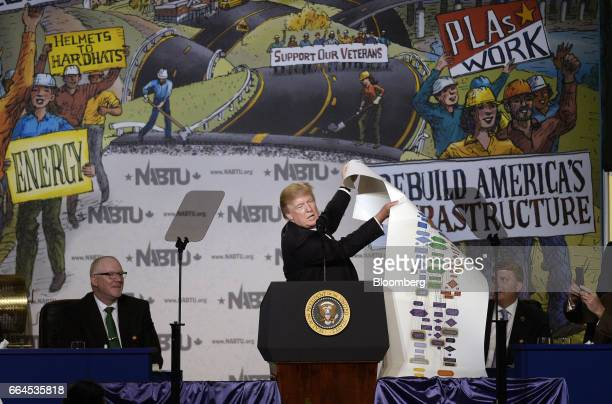 US President Donald Trump center speaks while holding up a chart during the 2017 North America's Building Trades Unions National Legislative...
