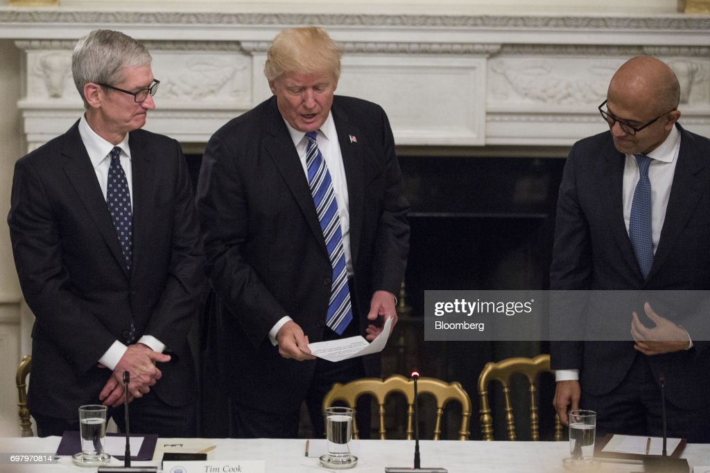 U.S. President Donald Trump, center, Tim Cook, chief executive officer of Apple Inc., left, and Satya Nadella, chief executive officer of Microsoft Corp., arrive for the American Technology Council roundtable hosted at the White House in Washington, D.C., U.S., on Monday, June 19, 2017. Executives from many of the world's largest technology companies gathered for the first meeting of the American Technology Council with Trump and his senior advisers. Photographer: Zach Gibson/Bloomberg via Getty Images