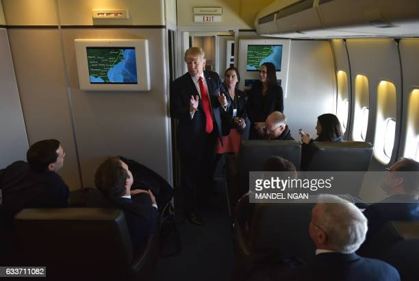 US President Donald Trump chats with reporters on board Air Force One before departing from Andrews Air Force Base in Maryland bound for Palm Beach...