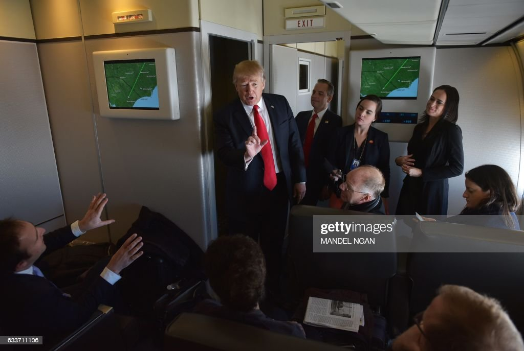 President Donald Trump chats with reporters on board Air Force One before departing from Andrews Air Force Base in Maryland, bound for Palm Beach, Florida on February 3, 2017. / AFP / Mandel Ngan