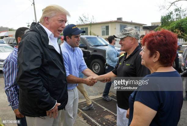 US President Donald Trump chats with residents in a storm damaged area in Guaynabo Puerto Rico on October 3 2017 Nearly two weeks after Hurricane...