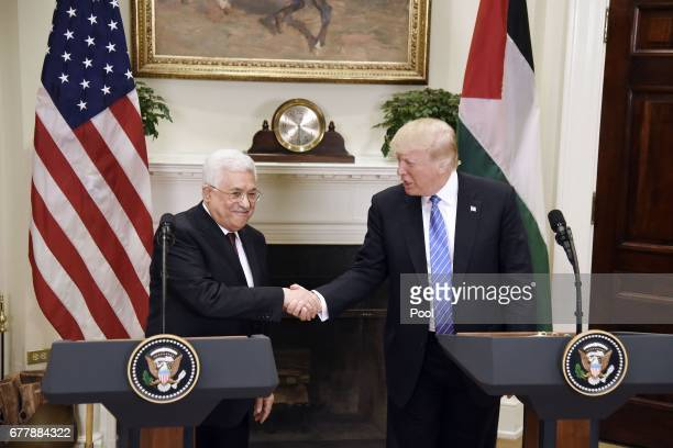 President Donald Trump checks hands with President Mahmoud Abbas of the Palestinian Authority after a joint statement in the Roosevelt Room of the...
