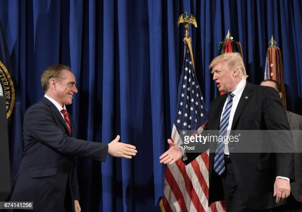 US President Donald Trump checks hands with Secretary of Veterans Affairs David Shulkin before giving remarks and signing an Executive Order on...