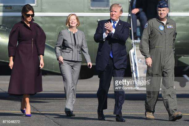 US President Donald Trump claps as he and First Lady Melania Trump walk to board Air Force One prior to departing from US Yokota Air Base in Tokyo on...