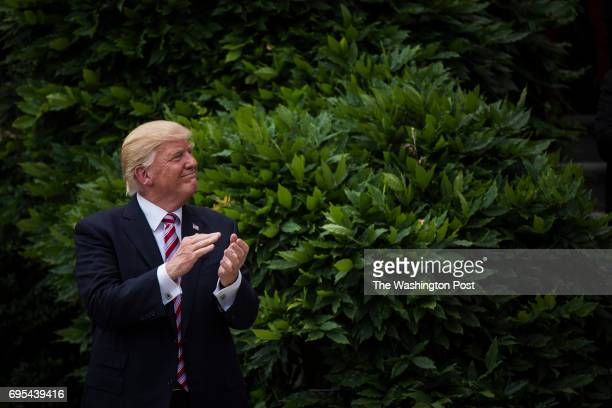 President Donald Trump claps during a ceremony on the South Lawn where the president honored the 2016 NCAA Football National Champions Clemson...