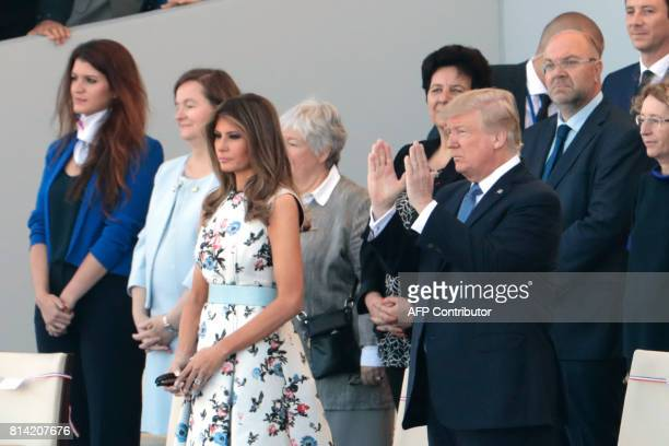 US President Donald Trump claps next to US First Lady Melania Trump during the annual Bastille Day military parade on the ChampsElysees avenue in...