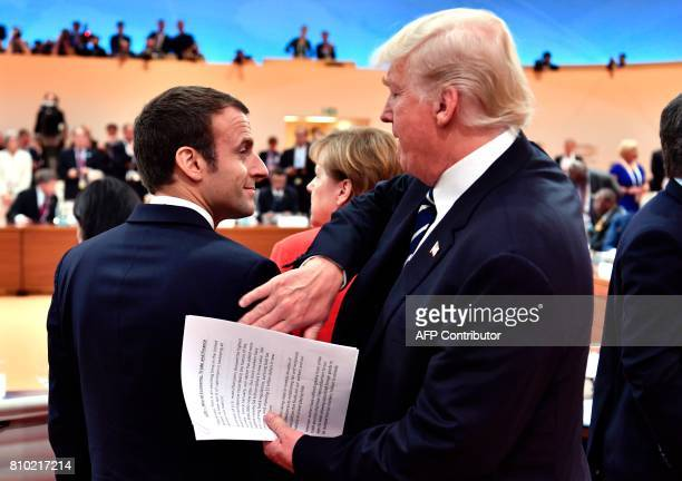 US President Donald Trump claps the shoulder of French President Emmanuel Macron at the start of the first working session of the G20 meeting in...