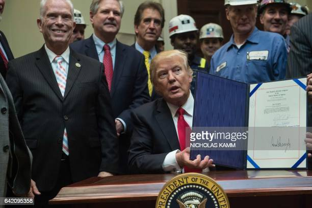 US President Donald Trump displays a bill he just signed eliminating regulations on the mining industry in the Roosevelt Room at the White House in...