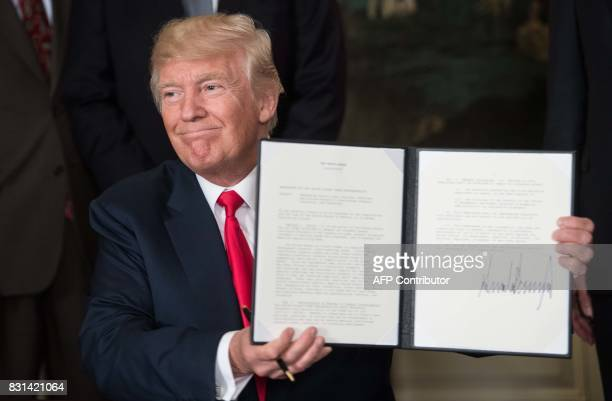 US President Donald Trump displays a memorandum on addressing Chinas laws policies practices and actions related to intellectual property innovation...