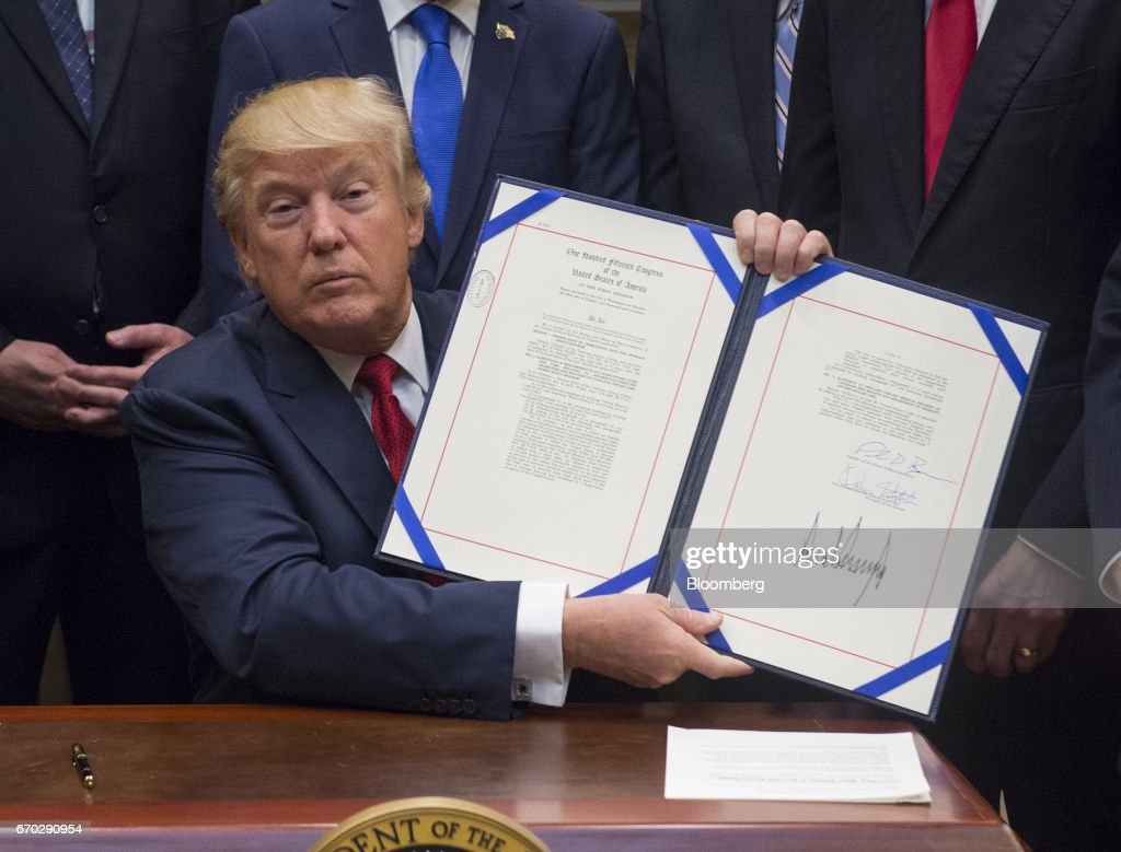 U.S. President Donald Trump displays bill S. 544, the Veterans Choice Program Extension and Improvement Act, after signing it in the Roosevelt Room of the White House in Washington, D.C., U.S., on Wednesday, April 19, 2017 The bill extends a program allowing eligible veterans to seek medical care from private health-care providers. Photographer: Molly Riley/Pool via Bloomberg