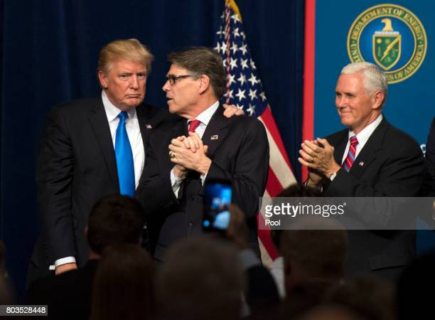 US President Donald Trump embraces Energy Secretary Rick Perry as Vice President Mike Pence applauds after Trump delivered remarks on at the...
