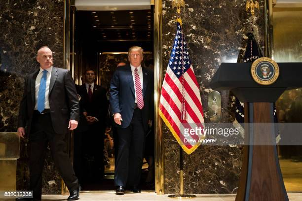 President Donald Trump emerges from the elevator to deliver remarks following a meeting on infrastructure at Trump Tower August 15 2017 in New York...