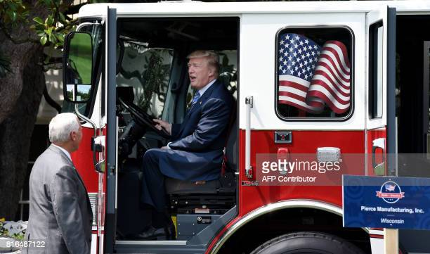 President Donald Trump examines a fire truck from Wisconsinbased manufacturer Pierce as Vice President Mike Pence looks on during a 'Made in America'...