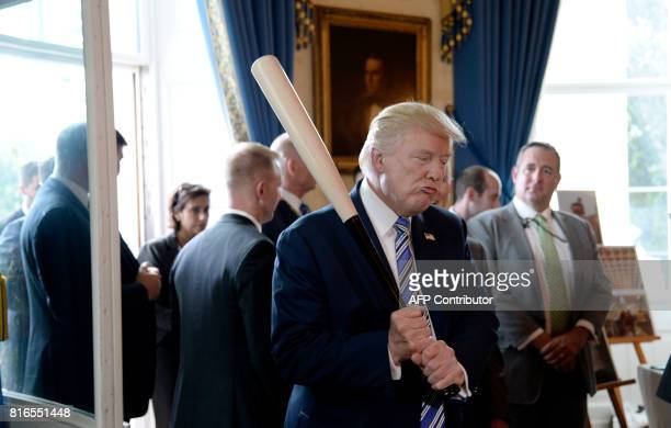 President Donald Trump examines USmade products from all 50 states including a Marucci baseball bat in the Blue Room of the White House during a...